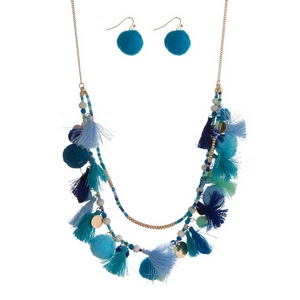 """Gold tone necklace featuring light blue, mint and royal blue tassels, beads and pom poms. Approximately 24"""" in length."""
