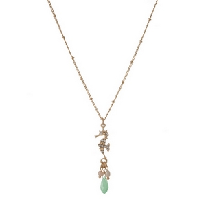 "Dainty gold tone necklace featuring a seahorse pendant, accented with a pale green and freshwater pearl bead. Approximately 16"" in length."