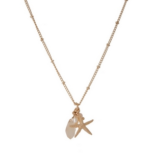 "Dainty gold tone necklace featuring a starfish pendant, accented with an ivory and freshwater pearl bead. Approximately 16"" in length."