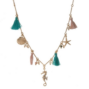 "Gold tone necklace featuring sea life charms and mint green and peach tassels. Approximately 16"" in length."