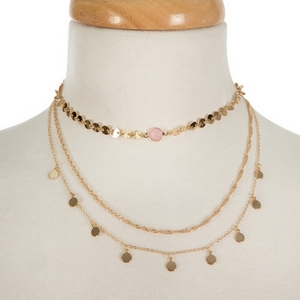 """Dainty three layer, gold tone choker featuring a pink stone focal. Approximately 12"""" to 16"""" in length."""
