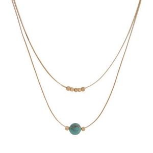"""Gold tone, two layer necklace with a turquoise natural stone bead. Approximately 14"""" and 16"""" in length."""