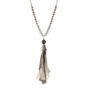 "Burnished silver tone necklace featuring an ivory and gray fabric tassel pendant and gray beads. Approximately 32"" in length."