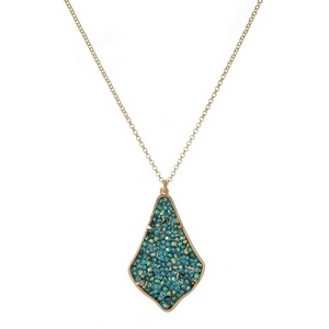 "Gold tone necklace featuring teardrop shaped pendant embellished with turquoise and mint green rhinestones. Approximately 32"" in length."
