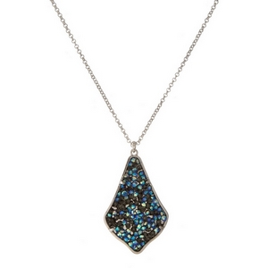 "Silver tone necklace featuring teardrop shaped pendant embellished with black and blue iridescent rhinestones. Approximately 32"" in length."