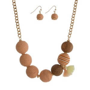 """Gold tone necklace set with peach thread wrapped balls and a tassel accent. Approximately 16"""" in length."""