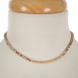 """Gold tone, dainty choker featuring gray faceted beads and a hammered bar focal. Approximately 12"""" in length."""
