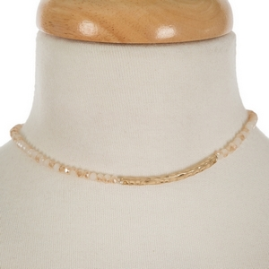 """Gold tone, dainty choker featuring ivory faceted beads and a hammered bar focal. Approximately 12"""" in length."""