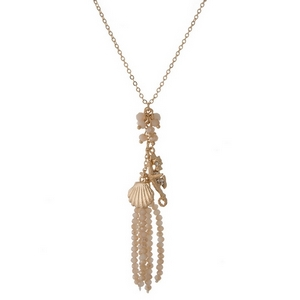 "Gold tone necklace featuring an ivory beaded tassel pendant, accented with seashell, starfish, and seahorse charms. Approximately 20"" in length."