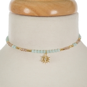 """Gold tone memory wire choker featuring mint green and iridescent beads and a star pendant. Approximately 5"""" in diameter. Handmade in the USA."""