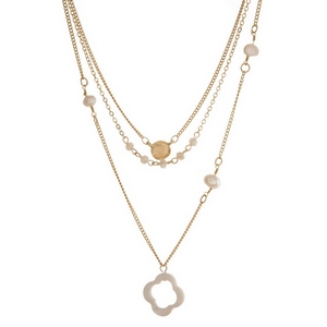 """Dainty gold tone, three layer necklace featuring freshwater pearl beads and a clover pendant. Approximately 16"""" to 20"""" in length."""
