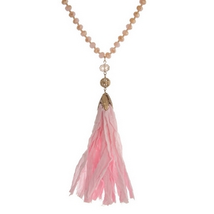 """Pink beaded necklace featuring a pink tassel and gold tone accents. Approximately 34"""" in length."""