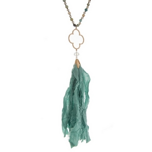"""Amazonite beaded necklace with a gold tone clover pendant and a mint green fabric tassel. Approximately 34"""" in length."""
