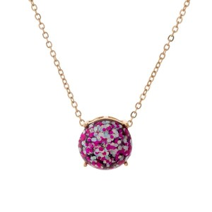 "Gold tone necklace with a fuchsia glitter, circle pendant. Approximately 16"" in length."