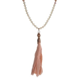 """Pink and peach beaded necklace with a peach fabric tassel and rose tone accents. Approximately 32"""" in length."""