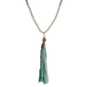 """Opal and mint green beaded necklace with a mint green fabric tassel and gold tone accents. Approximately 32"""" in length."""