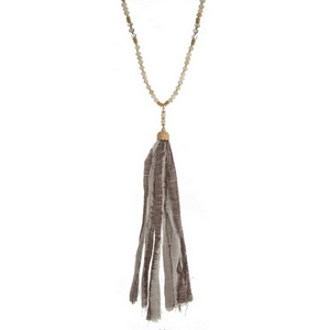 """Gold tone necklace with an ivory beaded chain and a gray fabric tassel. Necklace is approximately 34"""" in length and tassel is 8"""" in length."""