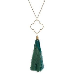 """Gold tone necklace with an open clover shaped pendant and a turquoise fabric tassel. Approximately 30"""" in length."""