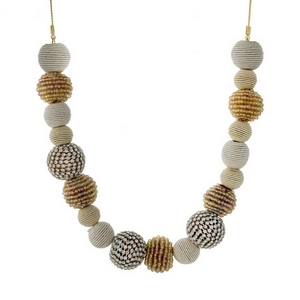 "Gold tone necklace with ivory thread wrapped ball beads and topaz beaded accents. Approximately 18"" in length."