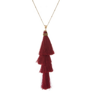"""Gold tone necklace with a tapered, burgundy thread tassel pendant. Approximately 30"""" in length."""