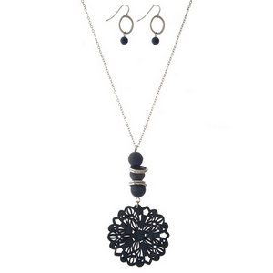"""Silver tone necklace set with a wooden, navy blue, laser cut pendant and natural stone accents. Approximately 32"""" in length."""