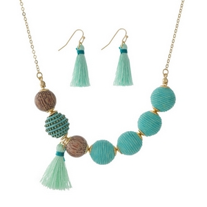 "Gold tone necklace set with mint green thread wrapped beads and wooden bead and tassel accents. Approximately 16"" in length."