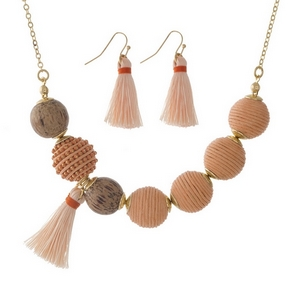 "Gold tone necklace set with peach thread wrapped beads and wooden bead and tassel accents. Approximately 16"" in length."