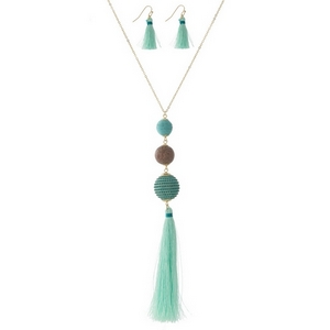 """Gold tone necklace set with a wooden bead, mint green thread wrapped ball bead, and a thread tassel. Approximately 30"""" in length."""
