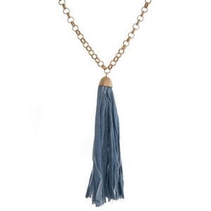 """Gold tone necklace with a light denim fabric tassel. Approximately 32"""" in length."""