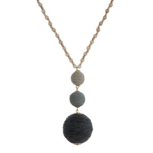 """Gold tone necklace with a gray to black ombre thread wrapped ball pendant. Approximately 30"""" in length."""