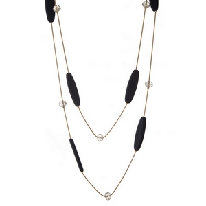"Gold tone two layer necklace with navy blue wooden beads and clear faceted bead accents. Approximately 24"" and 32"" in length."