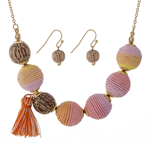 "Gold tone necklace with pink to orange ombre thread wrapped beads, wooden beads, a tassel accent and matching fishhook earrings. Approximately 16"" in length."