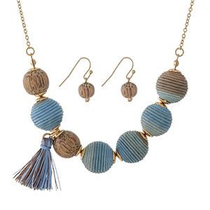 """Gold tone necklace with brown to blue ombre thread wrapped beads, wooden beads, a tassel accent and matching fishhook earrings. Approximately 16"""" in length."""