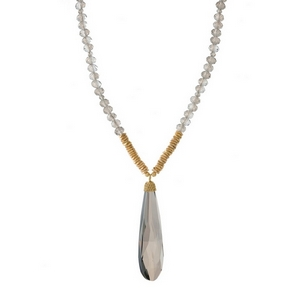 "Gray beaded necklace with a faceted stone pendant and gold tone accents. Approximately 32"" in length."