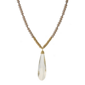 """Taupe beaded necklace with a faceted stone pendant and gold tone accents. Approximately 32"""" in length."""