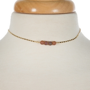 """Gold tone necklace with a peach druzy natural stone bar pendant. Approximately 13"""" in length."""
