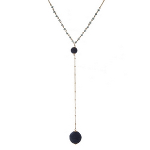 """Gold tone 'Y' necklace with navy blue beads and a thread wrapped bead pendant. Approximately 26"""" in length."""