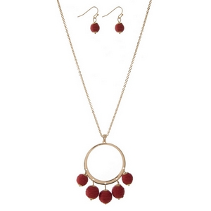 """Gold tone necklace set with an open circle pendant, red thread wrapped wrapped bead fringe, and matching fishhook earrings. Approximately 32"""" in length."""