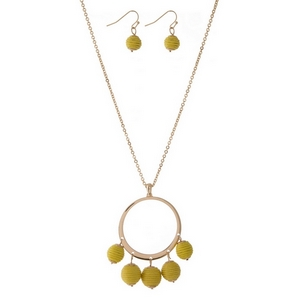 "Gold tone necklace set with an open circle pendant, yellow thread wrapped wrapped bead fringe, and matching fishhook earrings. Approximately 32"" in length."