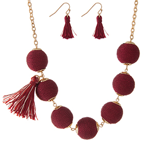 "Gold tone necklace set with burgundy thread wrapped beads, tassel accents and matching fishhook earrings. Approximately 16"" in length."