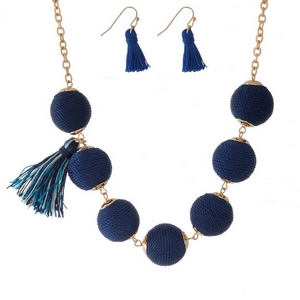 "Gold tone necklace set with navy blue thread wrapped beads, tassel accents and matching fishhook earrings. Approximately 16"" in length."