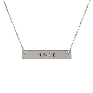 "Dainty silver tone, Breast Cancer Awareness necklace with a bar pendant, stamped with ""Hope."" Approximately 16"" in length."