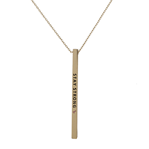 "Dainty gold tone, Breast Cancer Awareness necklace with a vertical bar pendant, stamped with ""Stay Strong."" Approximately 18"" in length."
