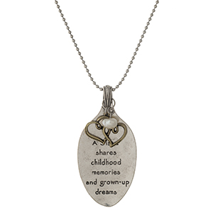 "Silver tone necklace with a spoon pendant, stamped with ""A sister shares childhood memories and grown-up dreams.""  Approximately 28"" in length."