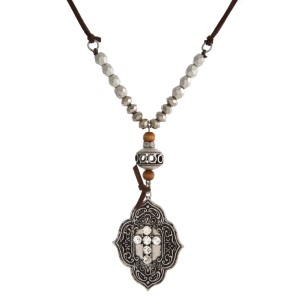 "Faux suede necklace with a half beaded body and a clear rhinestone cross pendant. Approximately 30"" in length."