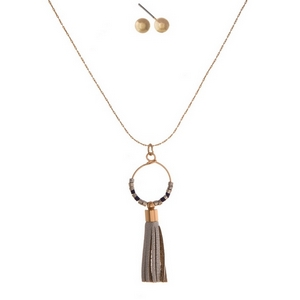 "Dainty, gold tone necklace set with a faux leather tassel pendant and matching stud earrings. Approximately 16"" in length."