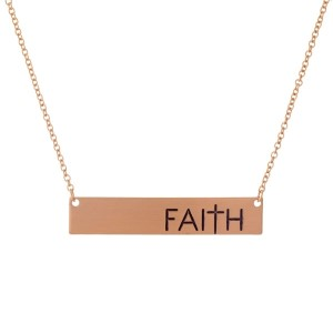 "Dainty rose gold tone necklace with a bar pendant, stamped with ""Faith."" Approximately 16"" in length."