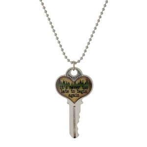 """Silver tone necklace with a key pendant that says """"It's never too late to begin again."""" Approximately 26"""" in length."""