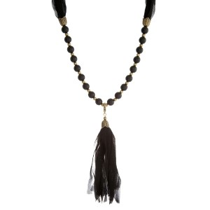 "Burnished gold tone necklace with black beads and a fabric tassel. This can be worn as a wrap bracelet by unclipping the tassel. Approximately 32"" in length."
