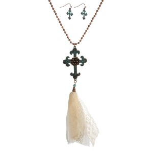 """Copper tone necklace with a patina cross pendant, an ivory fabric tassel and matching fishhook earrings. Approximately 32"""" in length."""